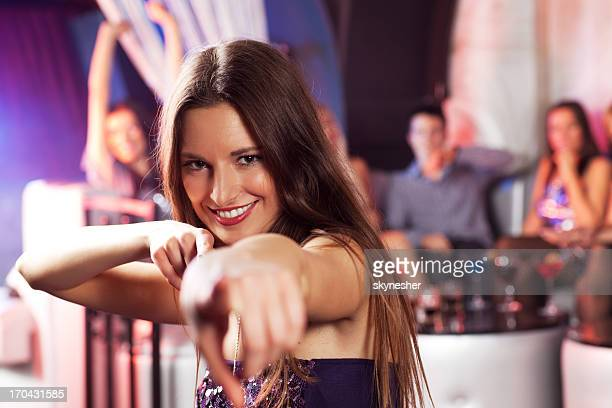 Beautiful brunette pointing finger at the camera in disco club.