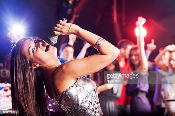 Schöne brunette singen mit Mikrofon in einem club.
