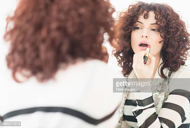 Beautiful brunette woman applying lipstick