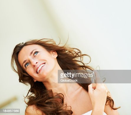 Beautiful brunette woman applying perfume to herself