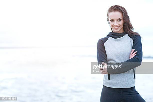 Beautiful brunette woman in dunes wearing sports clothes