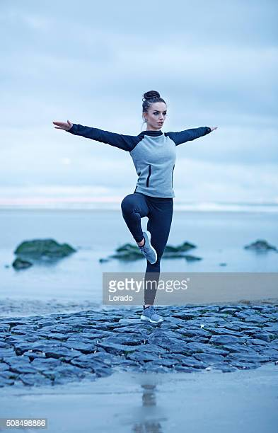 Beautiful brunette woman on a beach wearing sports clothes