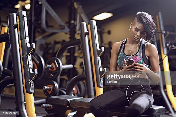 Beautiful brunette woman on smartphone during workout at gym