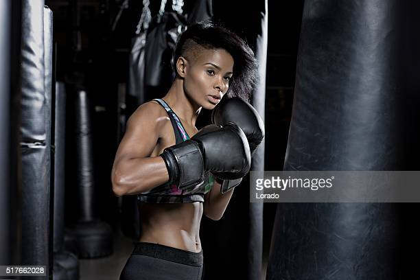 Beautiful brunette woman training during boxing workout at gym