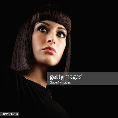 Beautiful Brunette Woman with Blunt Hairstyle on Black Backgroun