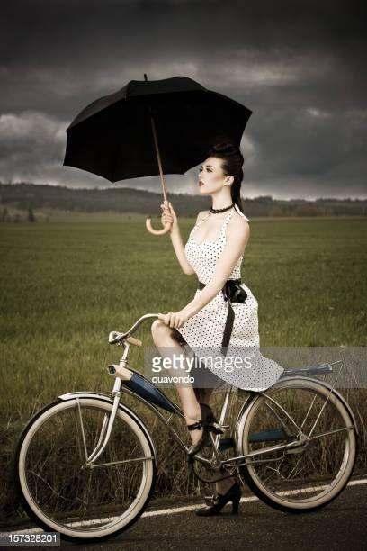 Brunette hermosa mujer joven montando bicicleta en vehemente clima antigüedades