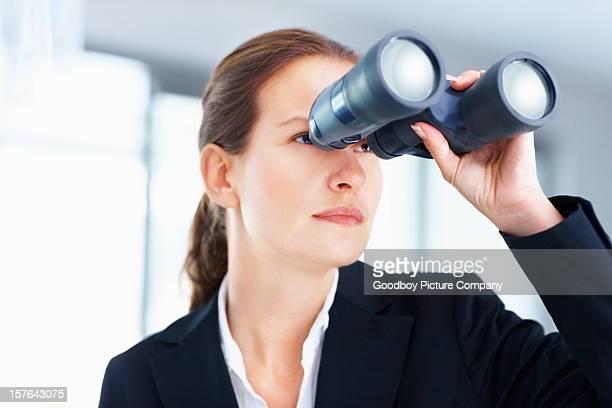 Beautiful business woman looking through binoculars