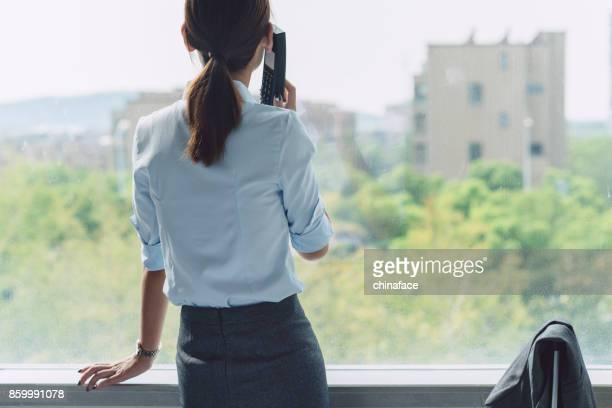 beautiful business woman talking on phone by window