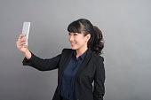 Beautiful business Woman using smartphone on grey background