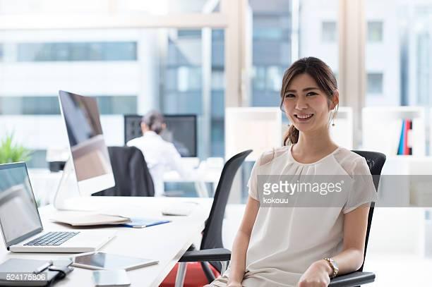 美しいビジネス女性のオフィスで働く
