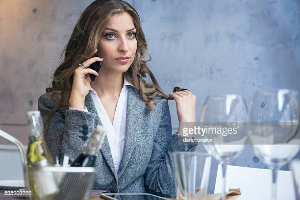 Beautiful businesswoman at restaurant talking on the phone