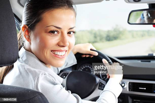 Beautiful businesswoman drive a car and looking at the camera.
