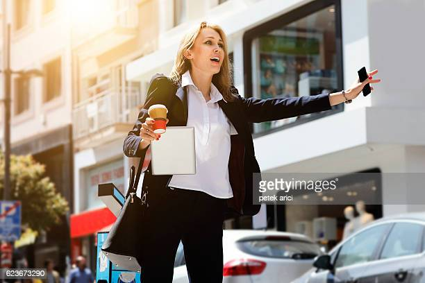Beautiful businesswoman hailing taxi in street
