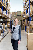 Beautiful businesswoman holding tablet in warehouse