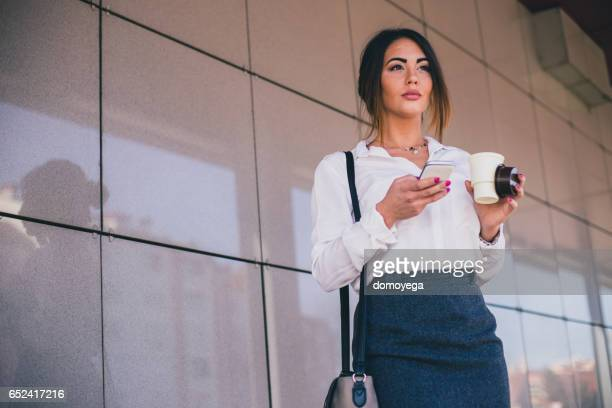 Beautiful businesswoman on a coffee break sending messages on her mobile phone