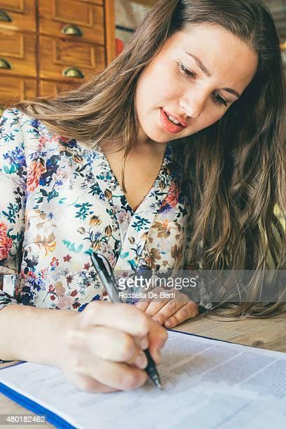 Schöne Geschäftsfrau Unterzeichnung Vertrag In einem Café im Innenbereich