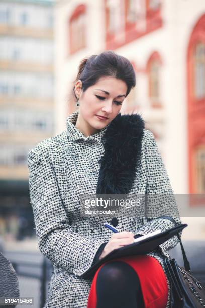 Beautiful businesswoman taking notes outdoors