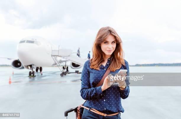 Schöne Geschäftsfrau mit einem Smartphone vor Flugzeug