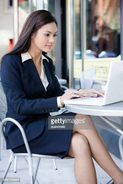 Beautiful Businesswoman Using Laptop at Outdoor Sidewalk Cafe, Copy Space