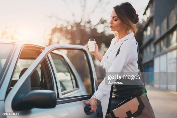 Beautiful businesswoman with a coffee to go entering the car