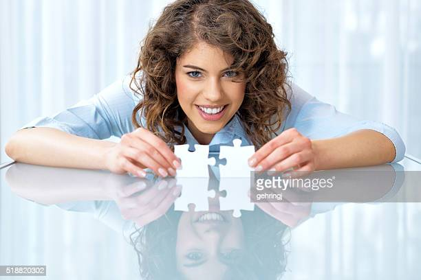 Beautiful businesswoman with puzzle