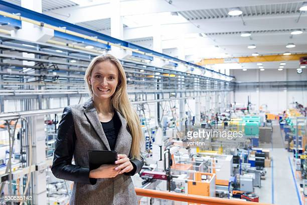 Beautiful businesswoman with tablet in factory