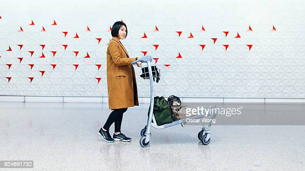 Beautiful businesswoman with trolley in airport