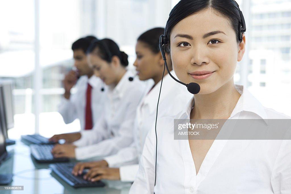 Beautiful call center operator at work place : Stock Photo
