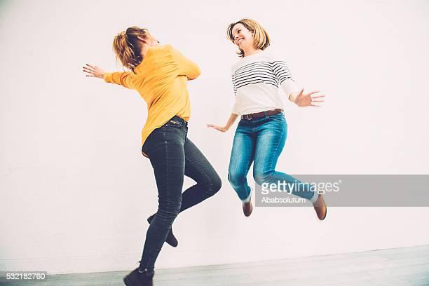 Schöne unbeschwerte junge Frauen springen, Paris, Frankreich