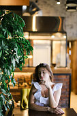 Beautiful caucasian girl resting at cafe and wearing white blouse with silver ring. Concept of beauty and rest.