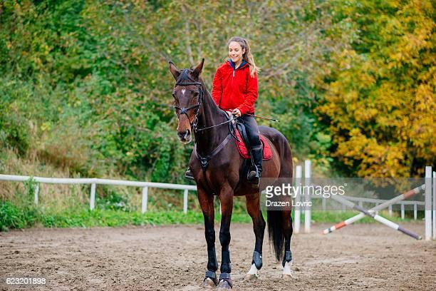 Beautiful caucasian horseback rider with mare
