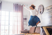 crazy happiness for beautiful woman jumping at home for great joy after a success or for a nice lifestyle. hippy chic bohemien clothes and bright funny image with winner concept