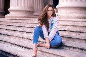 Young girl with brown hair and blue eyes, sits on old marble steps, dressed modern and looking at the camera.