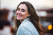 Close-up portrait of beautiful caucasian woman with charming smile walking outdoors