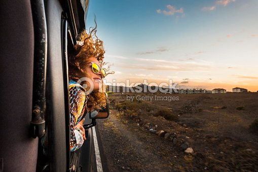 beautiful caucasian young woman travel outside the car with wind in the curly hair, motion and movement on the road discovering new places during a nice sunset, enjoy and joyful freedom concept : Stock Photo