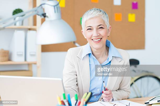 Beautiful cheerful mature woman at office working on computer