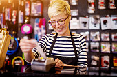 Beautiful cheerful woman while pulling out a check from the cashier.