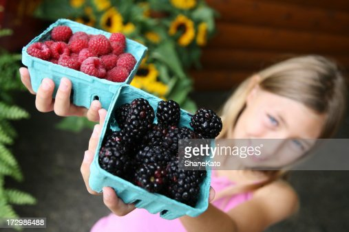 Beautiful child holds fresh produce at farmers market