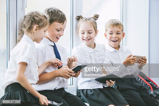 Beautiful children are students together in a classroom at the school receive education with tablets happy : Stock Photo