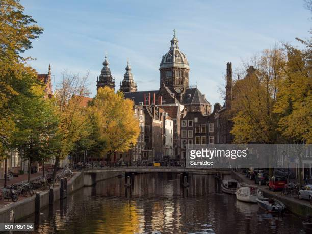 Beautiful cityscape in Amsterdam, Netherlands. Reflected city lights in water with blue sky. View of buildings and boats near the water in the canal. Wonderful view on house