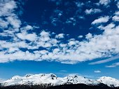 Beautiful cloudscape and snowy mountain ridges in front of Exit Glacier area at Kenai Fjords National Park in Seward Alaska USA
