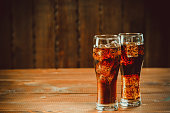 Beautiful cold fizzy cola soda with cubes ice in glasses goblet on old wooden background with free space. Shallow DOF.