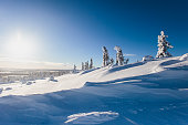 Beautiful cold mountain view of ski resort, sunny winter day with slope, piste and ski lift, Scandinavia, Lapland, blue sky