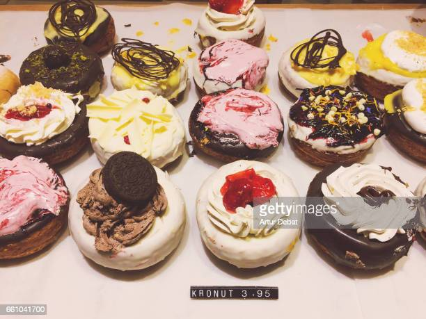 Beautiful colorful cronuts decorated with tasty sweet ingredients on the top in a chocolate store in Barcelona city.