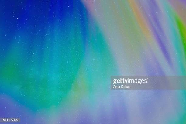 Beautiful colorful northern lights falling from the sky in Iceland in a stunning clear and nice lights with the sky full of stars. Aurora borealis.