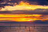 Abstract yellow sky, hidden red sun behind bright blue purple clouds, silhouettes of birds on sticks with wire sticking out of the water.