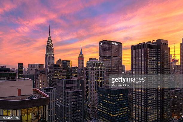 Beautiful colorful sunset over midtown Manhattan, viewed from a unique angle from a rooftop in NYC. Seeing the Empire State Building, Chrysler Building, MetLife Building.