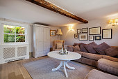 Stylish cottage living room containing sofa with large cushions, chic simple decor, numerous picture frames, coffee table, cupboard window and exposed beam