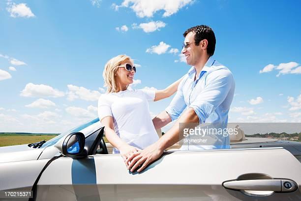 Schönes paar und Cabrio Auto gegen den blauen Himmel