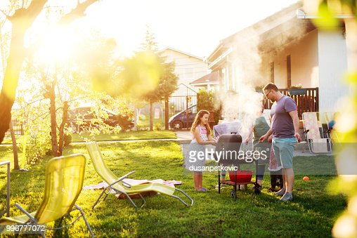 Beautiful couple and their adorable children have gathered around the grill  in front of the house. : Stock Photo